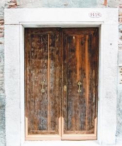 Condominio a Venezia, restauro portone ingresso in larice laccato 1